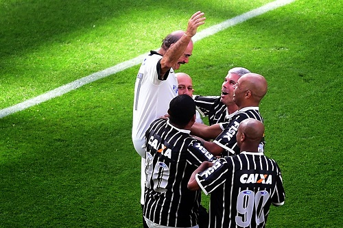 Jogadores comemorando o gol do Rivelino na Arena em jogo festivo